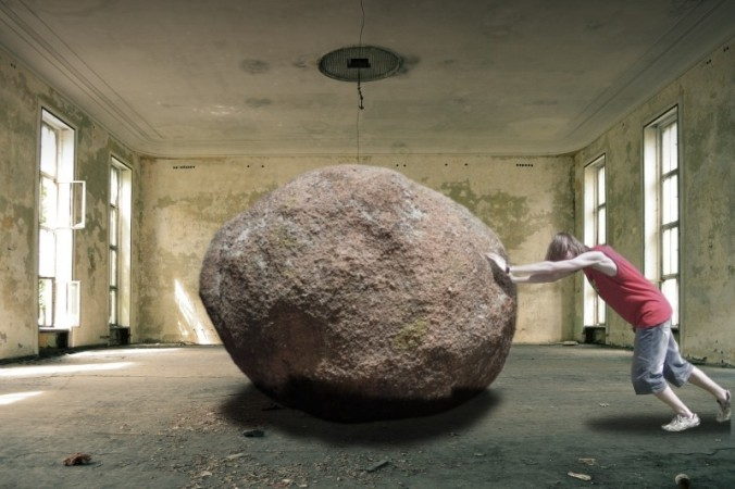 man-pushing-large-rock-in-empty-room